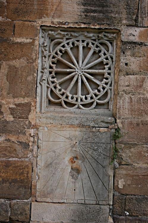 .....Sur un des murs de l'Eglise,un cadran solaire rapporté surmonté d'une rosace à 12 rayons.......