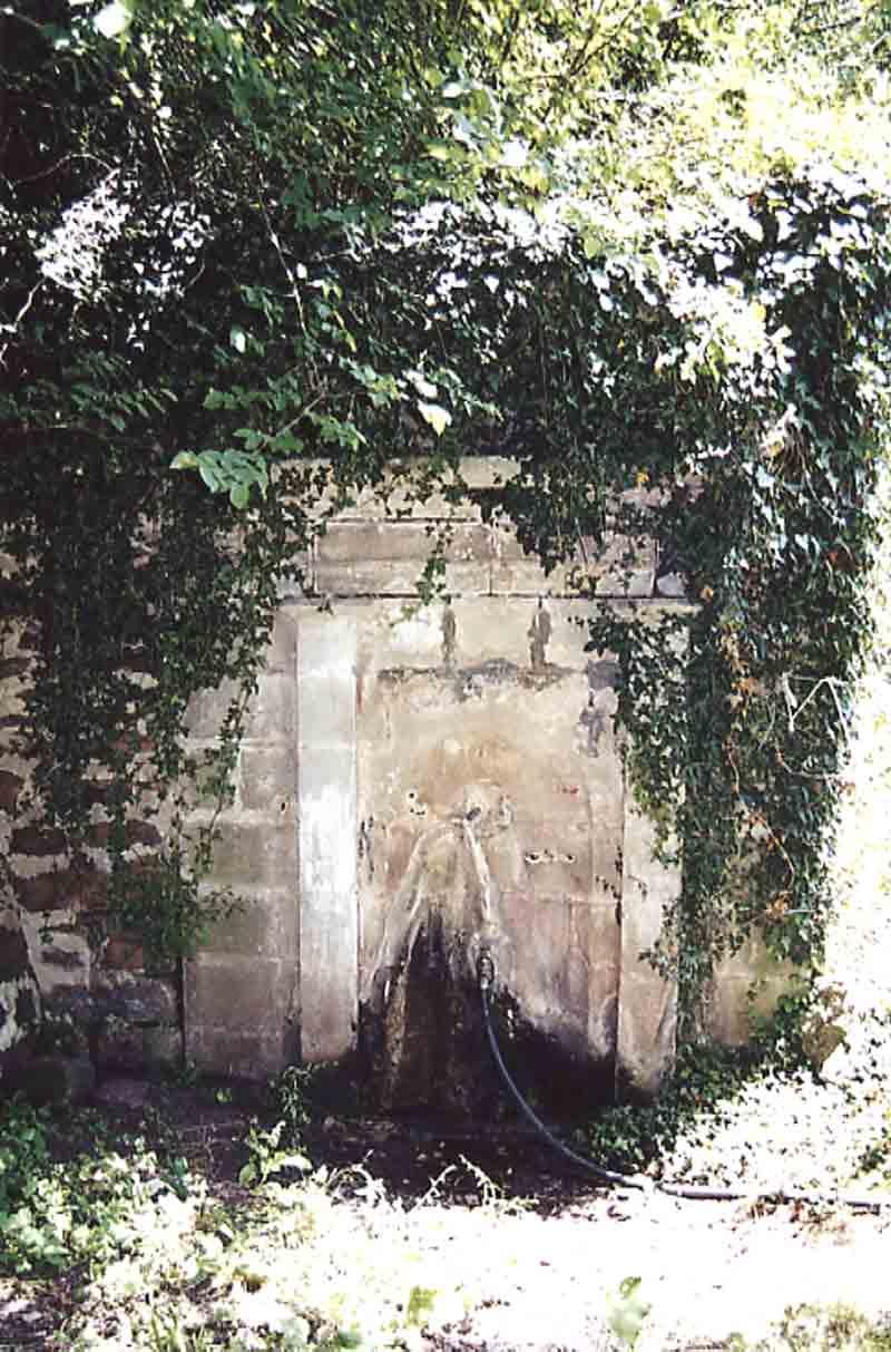 Une fontaine ancienne utilisée pour les jardins en bord de Sorgues avec des maisons en « vieilles pierres »