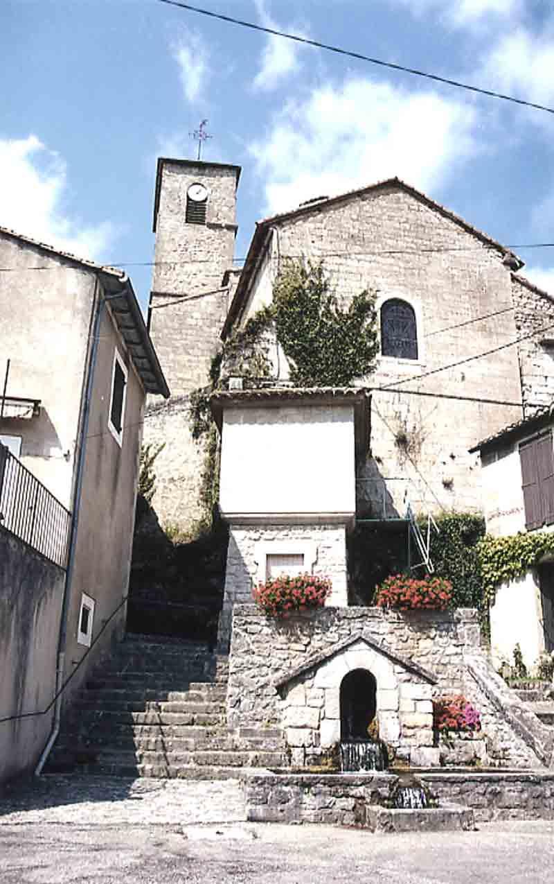 ...L'église vue de la place avec la fontaine ....