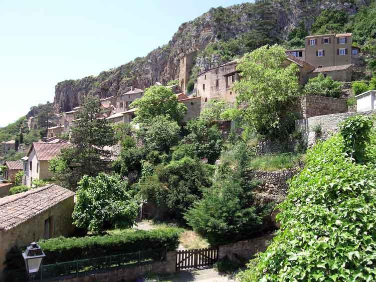 ......Village élaboré contre une falaise surmontée par un rocher dont certaines maisons sont construites à l'intérieur de celle-ci ....