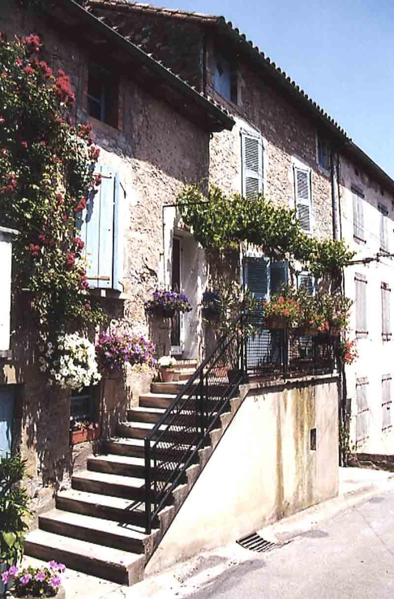 De l'autre côte de cette place , cette rue la traverse où l'on peut voir de très belles maisons fleuries …..