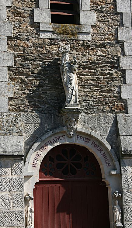 Intéressons nous de plus près à l'édifice : Dans la tribune extérieure du clocher , la Vierge en pierre , tenant dans ses bras le Divin Enfant . Le pèlerin est accueilli par Saint-Joseph et Sainte Jeanne d'Arc . Deux belles statues de pierre dues au ciseau de l'Artiste Roustan .